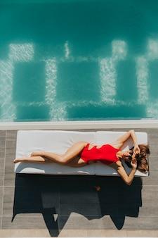 Jovem mulher deitada à beira da piscina na cama