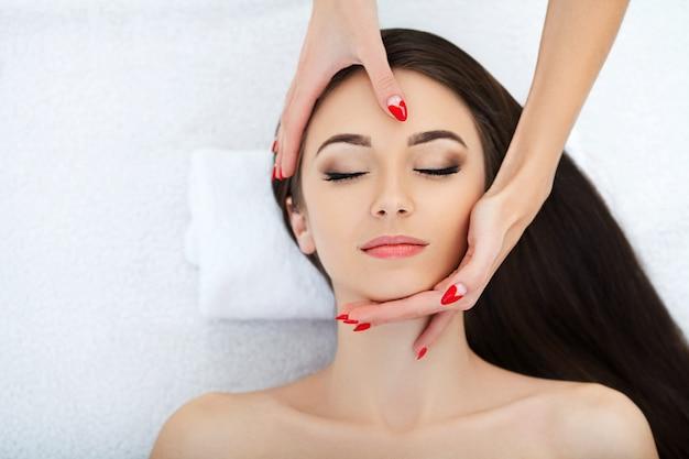 Jovem mulher deitada em uma mesa de massagem, relaxando com os olhos fechados. mulher. salão de spa