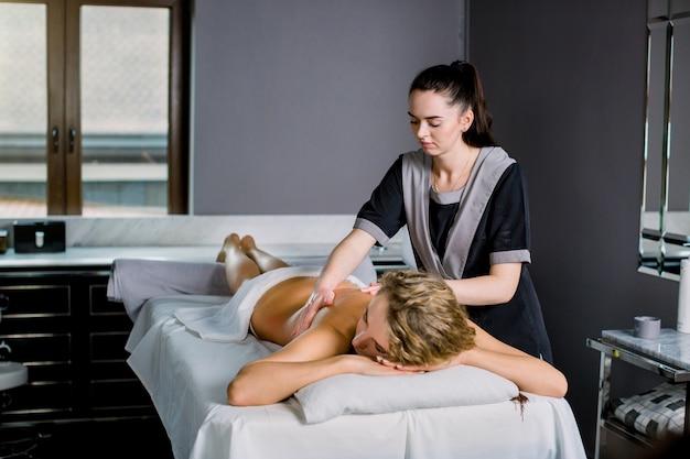 Jovem mulher deitada em uma mesa de massagem, relaxante, recebendo massagem nas costas manual profissional. massagista jovem fazendo massagem na mulher de volta ao centro médico