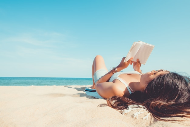 Jovem mulher deitada em uma praia tropical