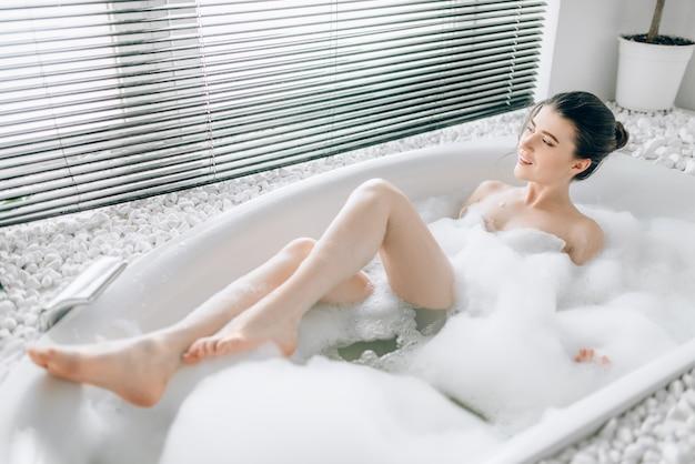 Jovem mulher deitada na banheira com espuma, vista borrada