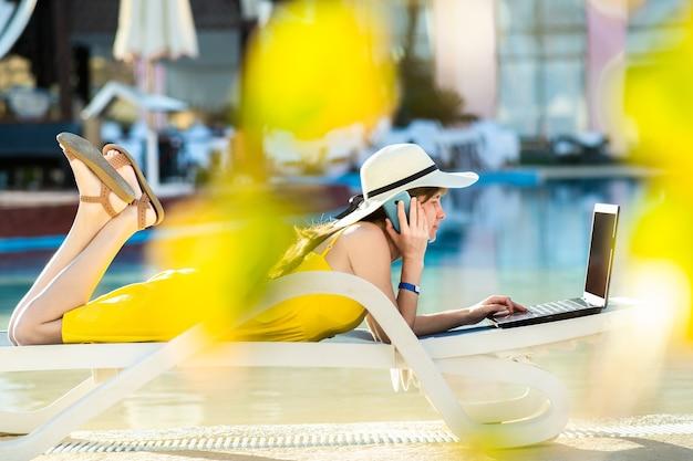 Jovem mulher deitada na cadeira de praia, trabalhando no computador laptop conectado à internet sem fio, tendo uma conversa no sellphone móvel no resort de verão. fazer negócios durante a viagem conceito.