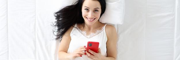 Jovem mulher deitada na cama com a vista de cima do telefone, conceito de folga