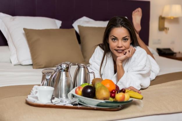 Jovem mulher deitada na cama com frutas e conjunto de café colocado perto