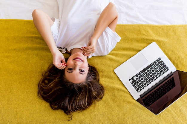 Jovem mulher deitada na cama com o laptop de cima. vista do topo.