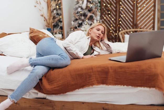 Jovem mulher deitada na cama com o laptop na época do natal.