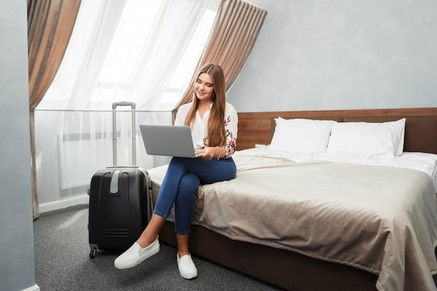 Jovem mulher deitada na cama de um quarto de hotel