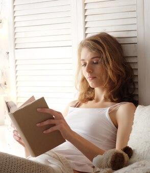 Jovem mulher deitada na cama enquanto lê um livro - bons momentos em casa