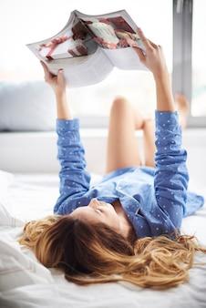 Jovem mulher deitada na cama lendo um livro
