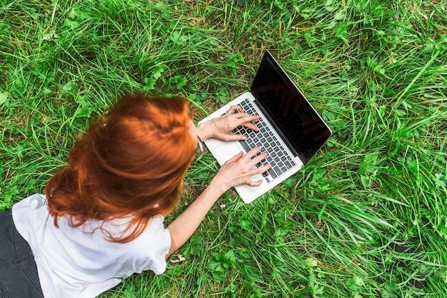 Jovem mulher deitada na grama brilhante com laptop