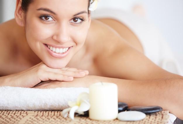 Jovem mulher deitada na mesa de massagem e sorrindo