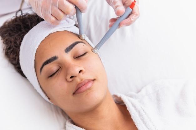 Jovem mulher deitada na mesa do cosmetologista durante o procedimento de rejuvenescimento. o cosmetologista cuida da juventude e do bem-estar da pele do pescoço e do rosto. procedimento de limpeza da face de hardware.