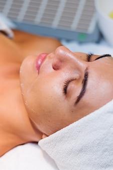 Jovem mulher deitada na mesa do cosmetologista durante o procedimento de rejuvenescimento