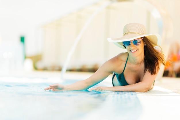 Jovem mulher deitada na piscina