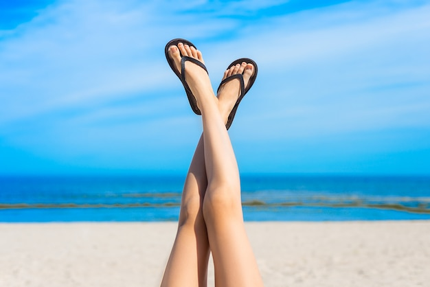 Jovem mulher deitada na praia, esticando as pernas delgadas. mar azul ao fundo.