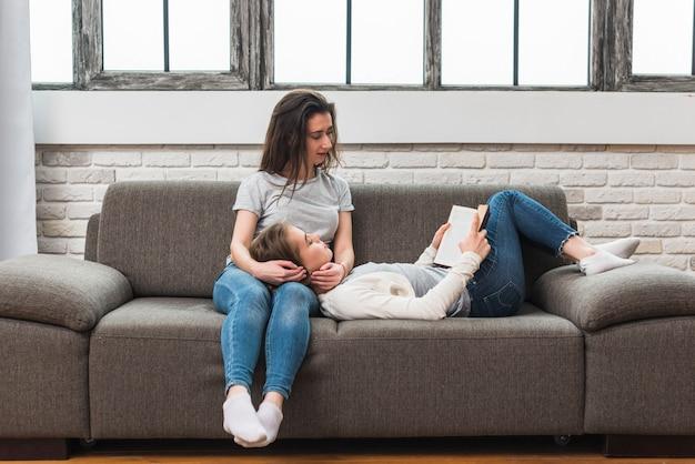 Jovem mulher deitada no colo da namorada, lendo o livro no sofá