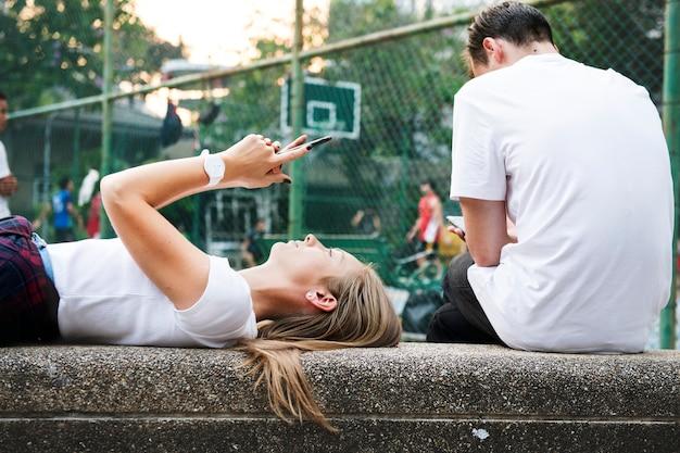 Jovem mulher deitada no parque usando um smartphone