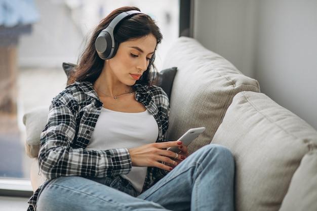 Jovem mulher deitada no sofá em fones de ouvido, ouvindo música
