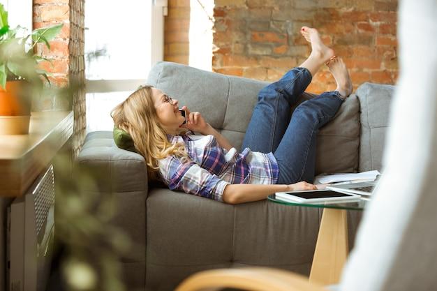Jovem mulher deitada no sofá, falando ao telefone.