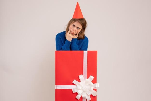 Jovem mulher dentro de uma caixa vermelha de presente com uma cara triste de frente