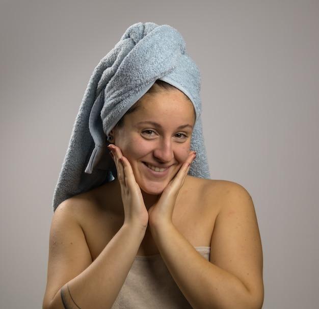 Jovem mulher depois do banho com uma toalha e feliz. tocando seu rosto