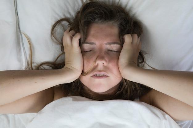 Jovem mulher deprimida e infeliz, deitada na cama com problemas de saúde, gritando, sobre depressão, desamparada