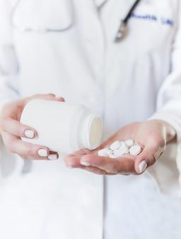 Jovem mulher derrama medicina, cápsula ou comprimido na mão dela.
