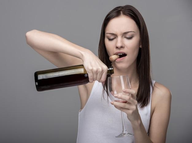 Jovem mulher derrama vinho em um copo.