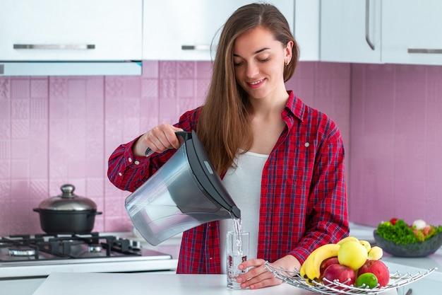 Jovem mulher derramando água filtrada fresca do filtro de água em um copo para beber na cozinha