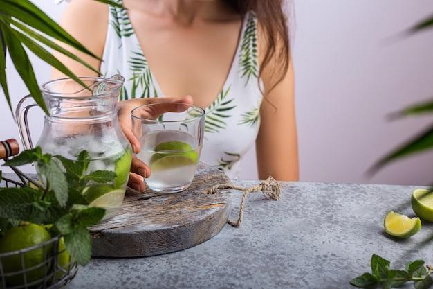 Jovem mulher derramando limonada fresca do jarro em vidro