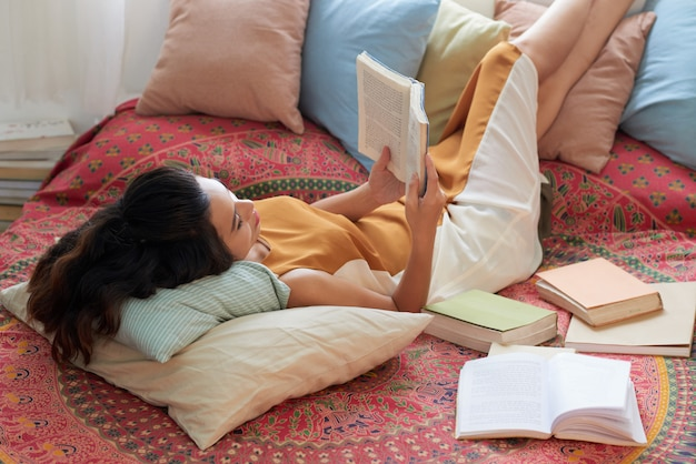 Jovem mulher descansando com o livro na cama com as pernas nas almofadas