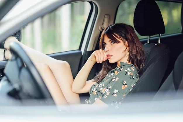 Jovem mulher descansando em um carro branco, puxando os pés pela janela.