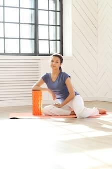 Jovem mulher descansando em um tapete de ioga