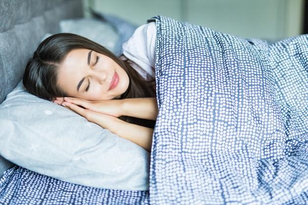 Jovem mulher descansando na cama com as mãos ao lado da cabeça no travesseiro.