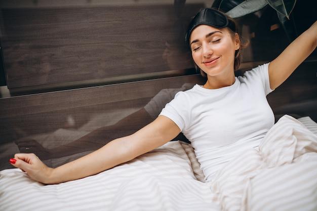 Jovem mulher descansando na cama de manhã