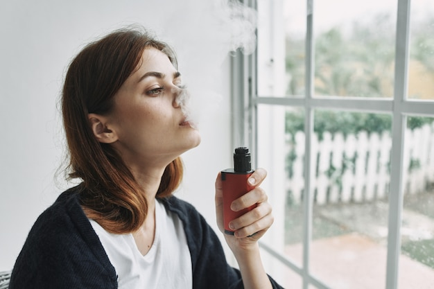 Jovem mulher descansando na poltrona em casa pela janela