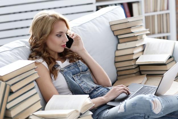 Jovem mulher descansando no sofá, falando por telefone