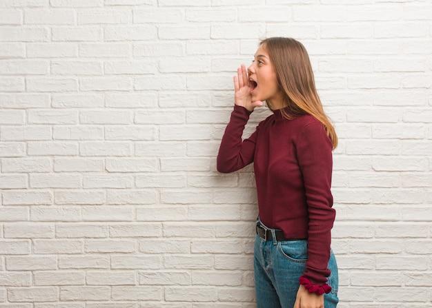 Jovem mulher descolada sobre uma parede de tijolos sussurrando um tom de fofoca