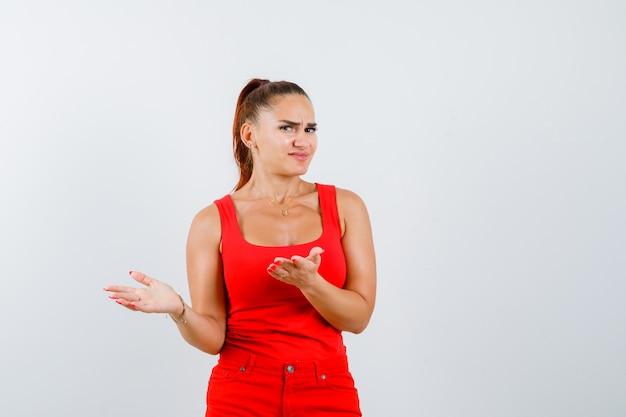 Jovem mulher descontente com a pergunta idiota em uma blusa vermelha, calça e parecendo confusa, vista frontal