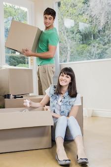 Jovem mulher desembalar caixas de papelão em casa nova