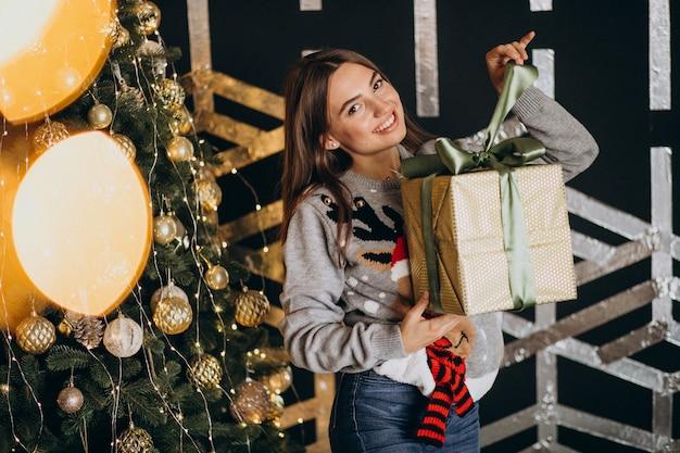 Jovem mulher desembalar presente de natal pela árvore de natal