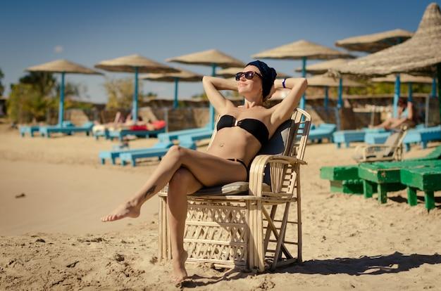 Jovem, mulher, desfrutando de sol na praia