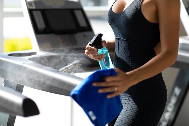 Jovem mulher desinfetando equipamentos de ginástica de fitness de limpeza com pulverizador de álcool.