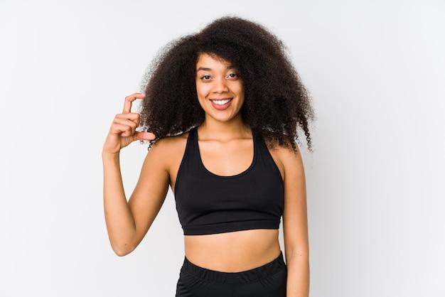 Jovem mulher desportiva afro-americana segurando algo pouco com o dedo indicador, sorrindo e confiante.