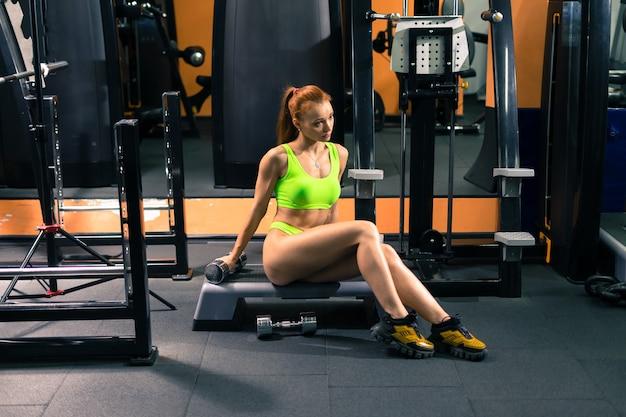 Jovem mulher desportiva, alongamento, treinamento na academia.