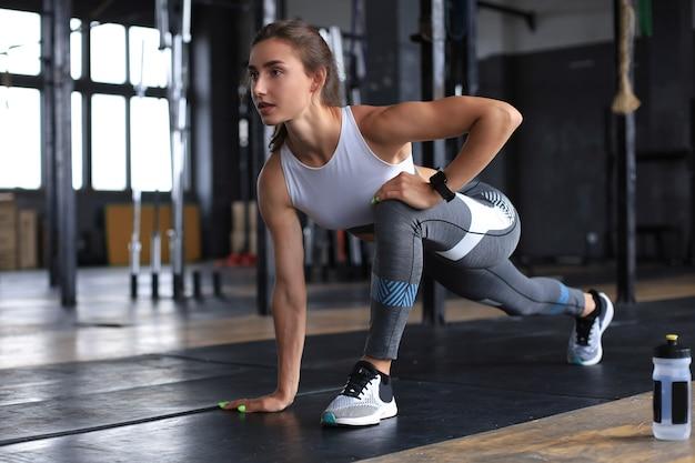 Jovem mulher desportiva alongando-se no ginásio.