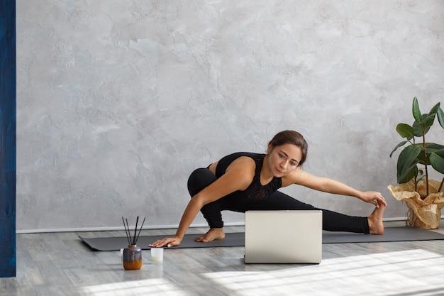Jovem mulher desportiva assistindo aulas de ioga online no laptop.