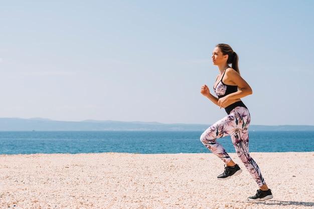 Jovem mulher desportiva ativa que corre ao longo do oceano