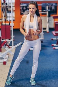 Jovem mulher desportiva bonita com corpo perfeito fazendo exercícios em uma academia