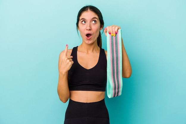 Jovem mulher desportiva, caucasiana, segurando elásticos isolados em um fundo azul apontando para cima com a boca aberta.